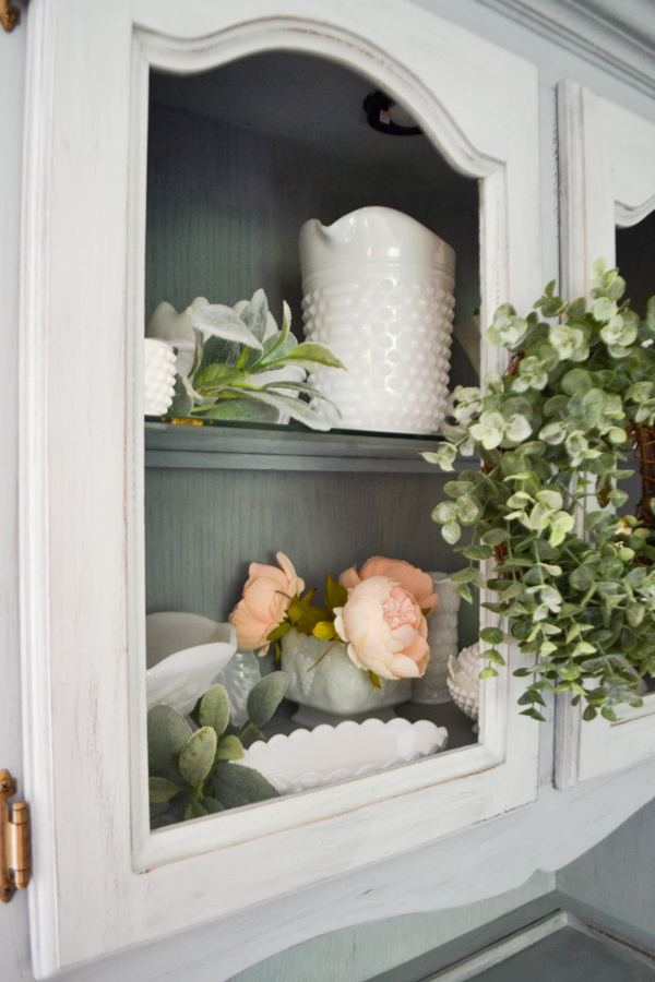 A close up of a a no glass front cabinet door with a milk glass collection and greenery displayed on the shelves