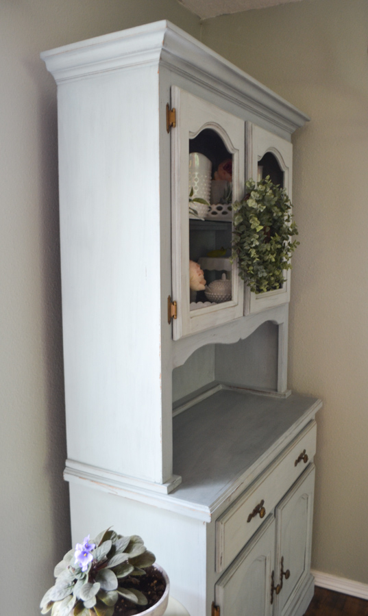 A side view of a blue gray milk painted hutch with a boxwood wreath hanging on the knobs on the front