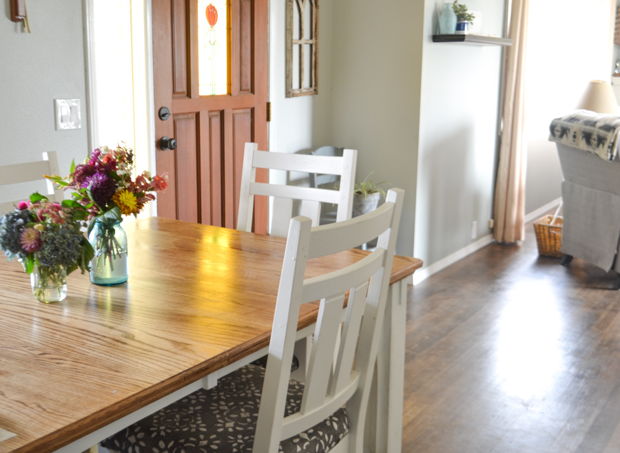 A side dining room shot with a brown front door and a dining table with two white chairs