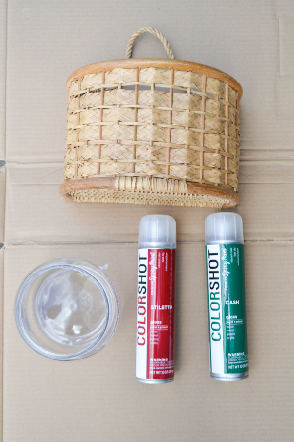 An above shot of a basket with a hanger, a plastic container and two cans of ColorShot spray paint in red and green