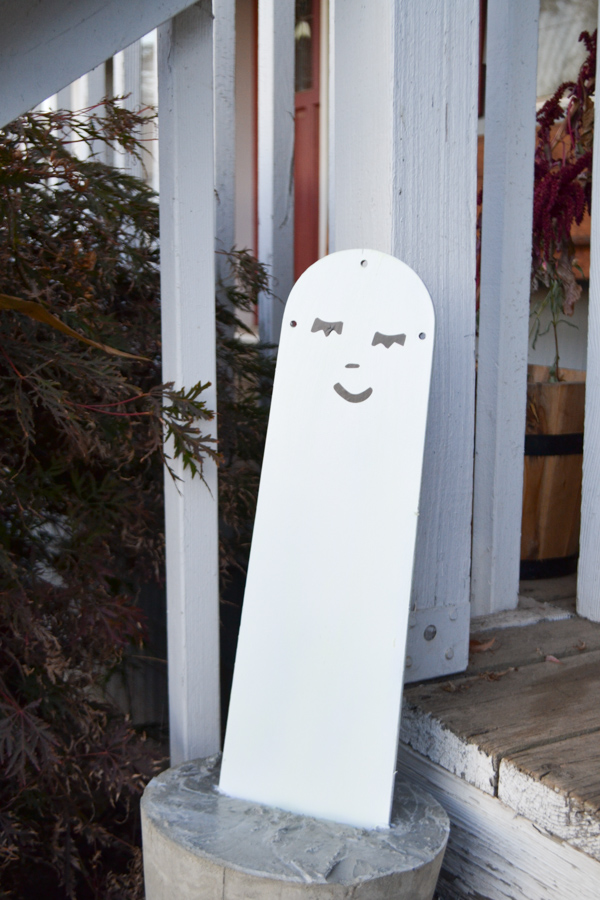A white painted fan blade in concrete sitting against a white porch, ghost is a girl face