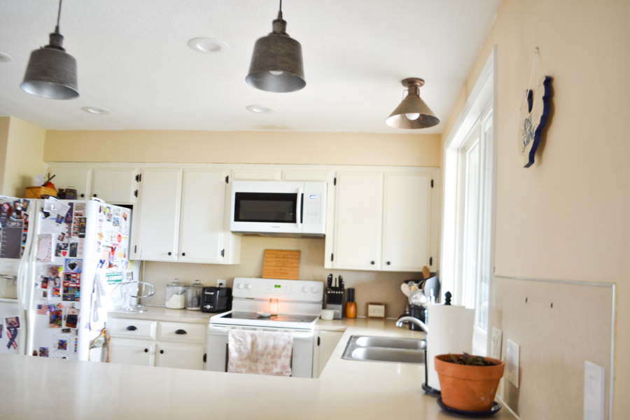 A side view close up with a kitchen counter in the foreground and white painted cabinets in the background with a sink on the right and a microwave above the stove