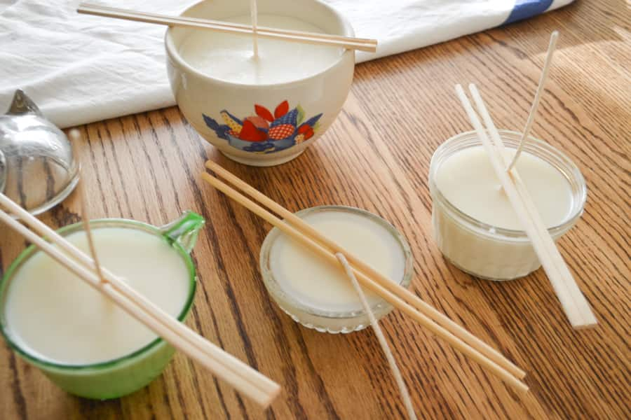 Multiple soy candle containers on a table top with long wicks and chopsticks holding the wicks