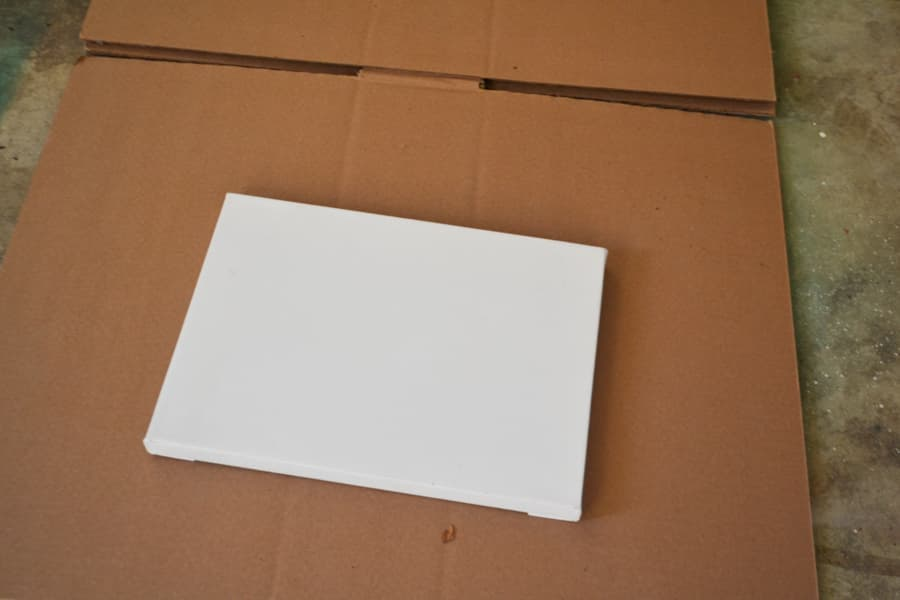 A white artists canvas laying on a piece of brown cardboard