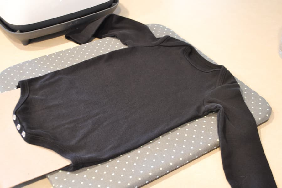 A black onesie laying on a grey pad with a piece of cardboard inside the onesie on a countertop