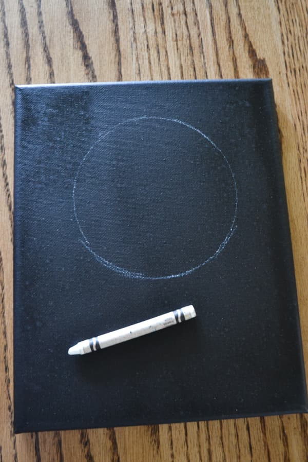 A black canvas with a white circle on the top half with a white crayon laying on the bottom half of the canvas