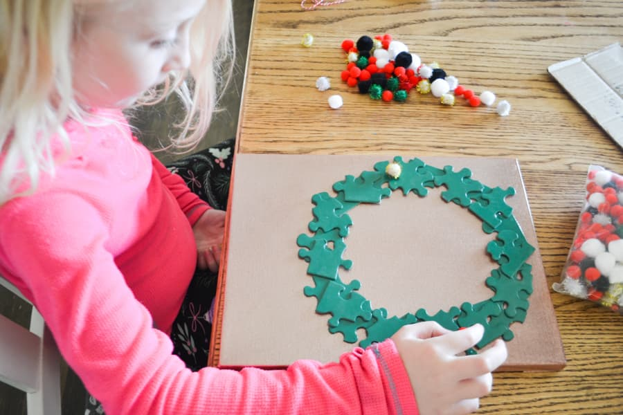 An above view of a girl gluing pom poms on a green puzzle piece wreath at a maple colored table