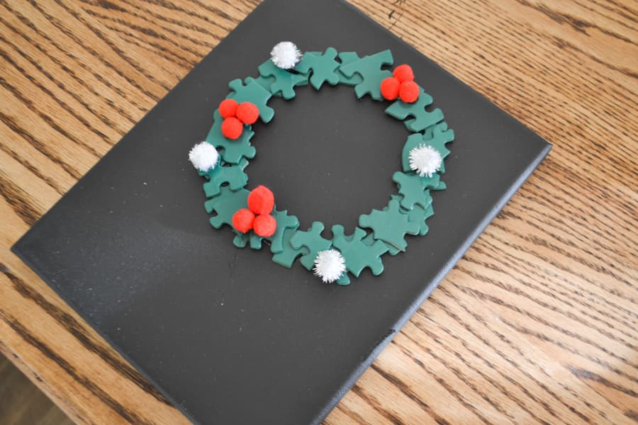 A black painted canvas with a green puzzle piece wreath glued on with red and white pom poms