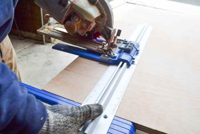 A circular saw attached to a Kreg Rip-Cut Jig with a man holding the jig against a sheet of plywood