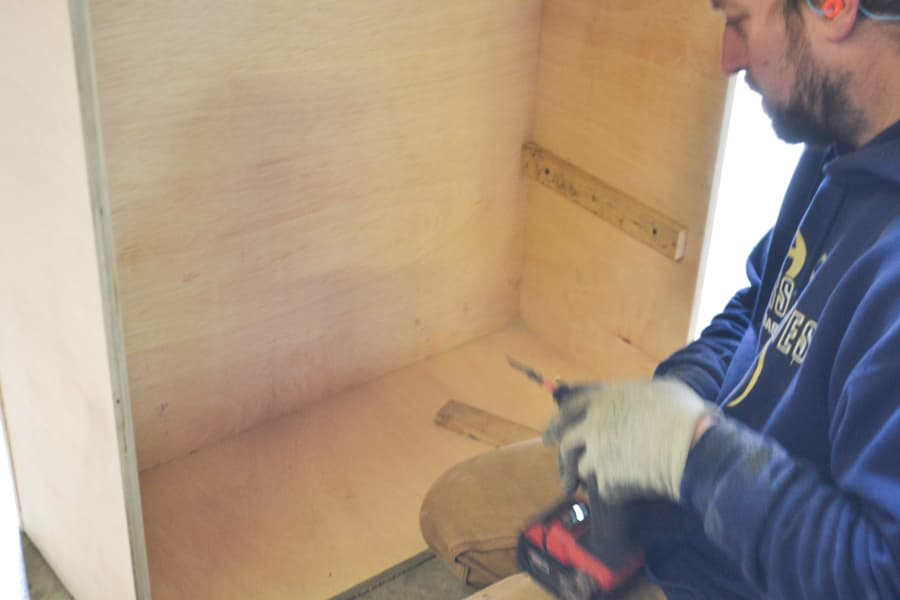 A side view of a man kneeling on the ground with a plywood shelving unit stood up with wood braces attached to the side
