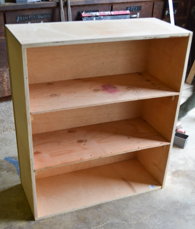 A two shelf unit with a top and bottom made of plywood sitting on a concrete floor