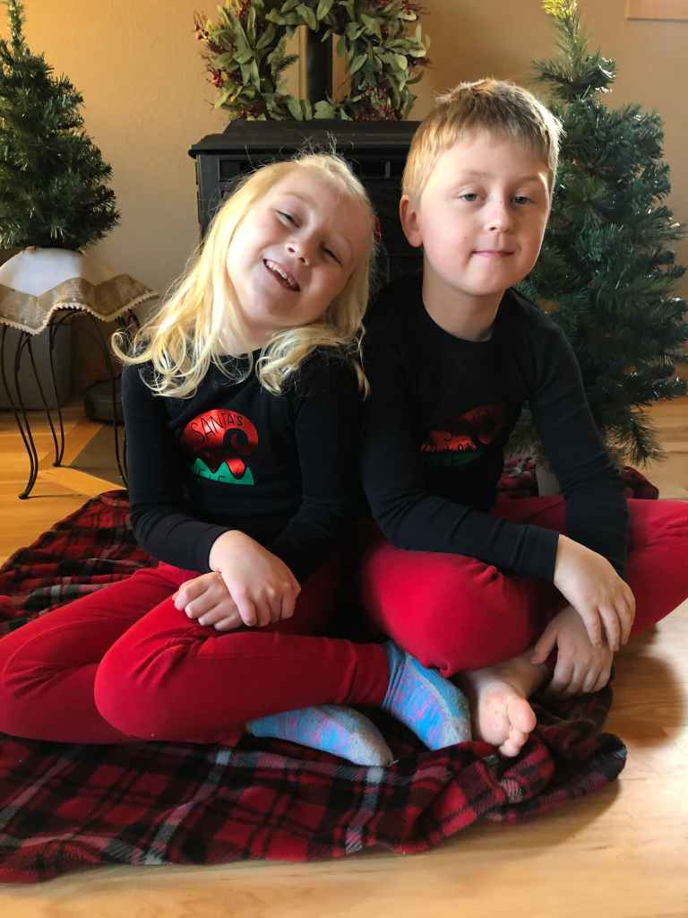 A blonde girl on the left and a boy on the right with matching black and red pajamas