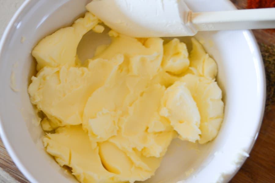 A white bowl with a stick of yellow butter mashed up with a white spatula inside the bowl