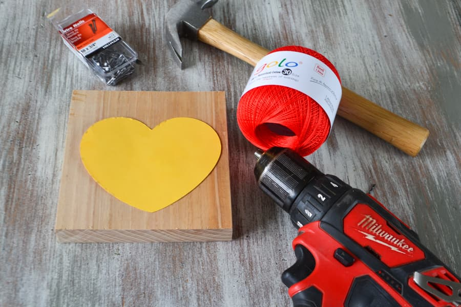 An unfinished wood block with a yellow paper heart on top laying next to a drill, a hammer, a red ball of string and a small plastic box of nails