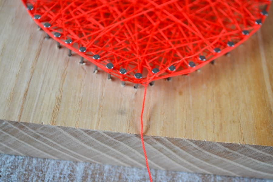 A close up of the edge of a completed string art to show the tie off of the last piece