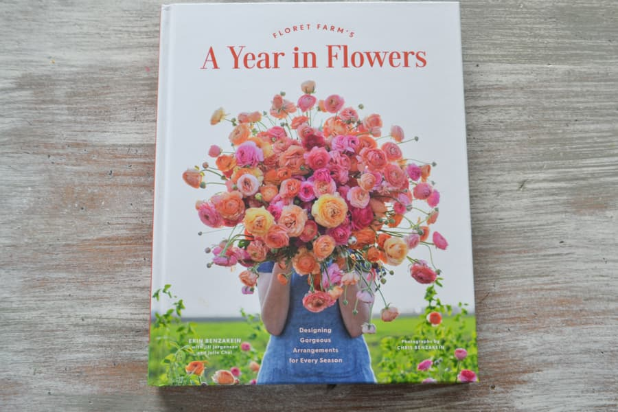 "A view from above of the book ""A Year in Flowers"" sitting on a whitewashed table"