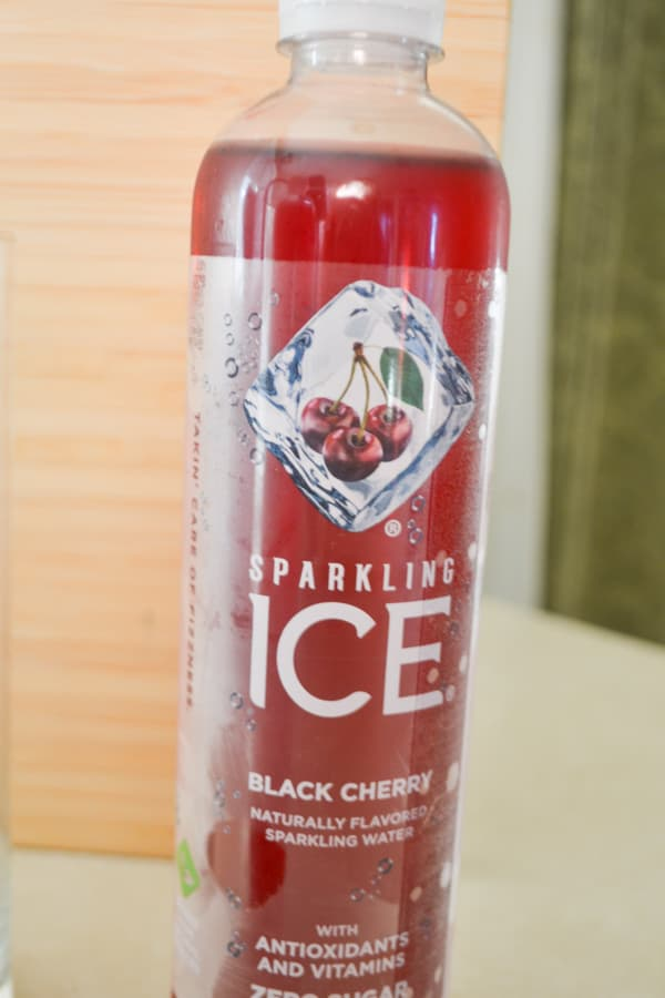 A bottle of black cherry sparkling ice water sitting on a counter against a wood background