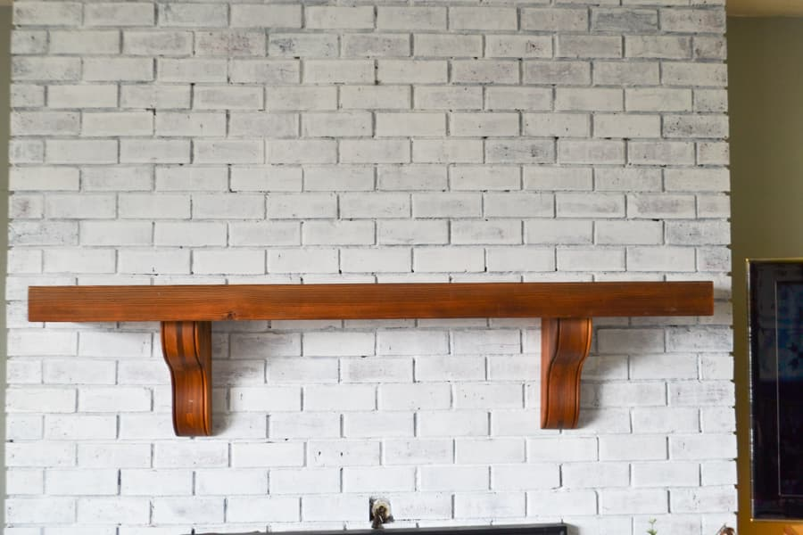 A view of a brown mantel that is bare on a white brick fireplace