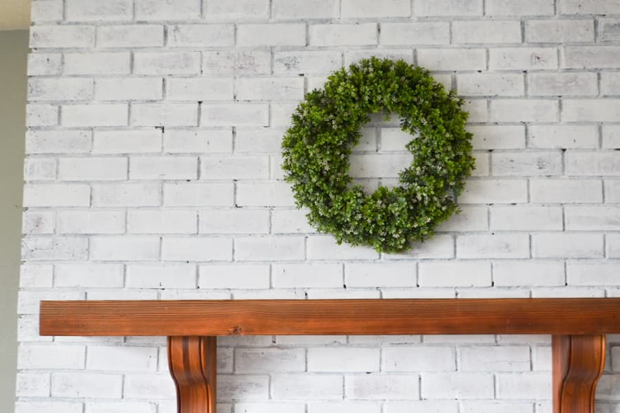 A brown wood mantel against a white brick fireplace with a green boxwood wreath hung in the middle