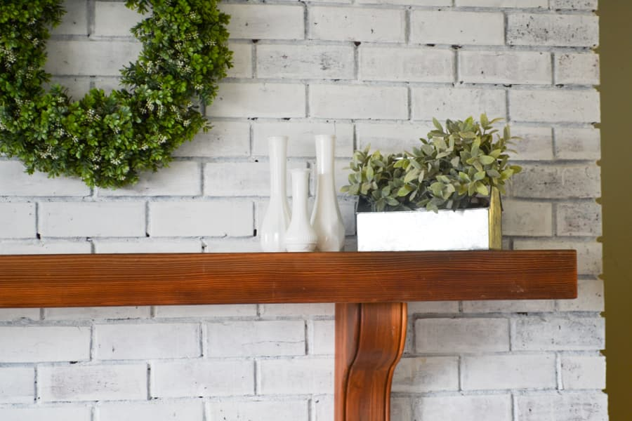 A close up of a brown mantel against a white brick fireplace with the edge of a boxwood wreath on the left and three milk glass vases and a metal tin with greenery on the right