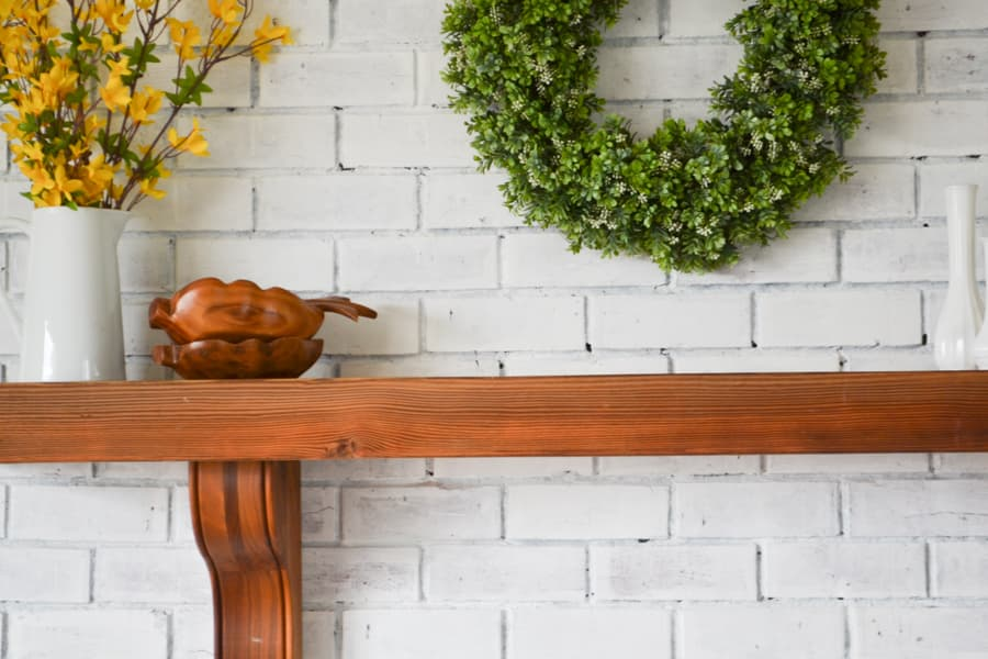 A brown mantel on a white brick fireplace with a white pitcher with yellow branches in it with a green boxwood wreath above