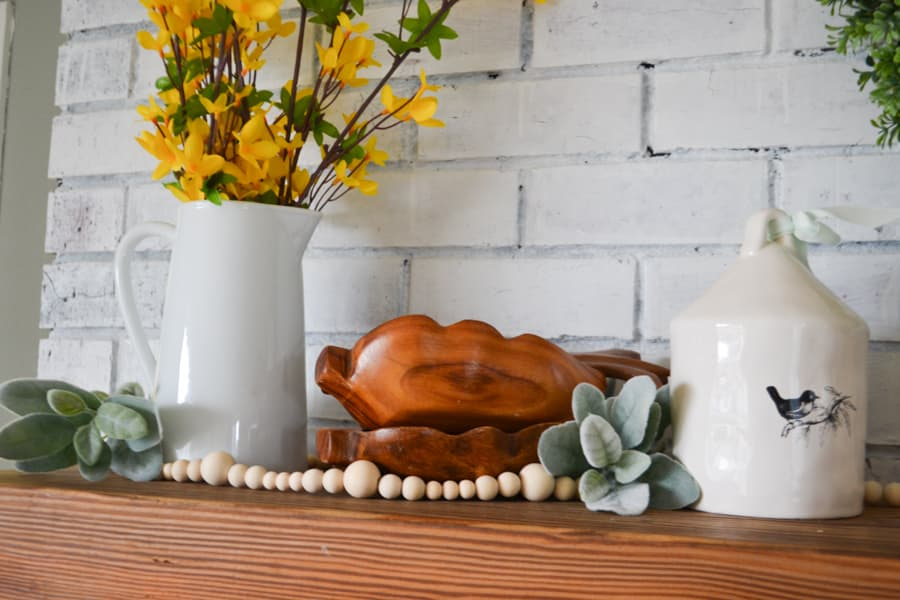 A close up of stacked wooden bowls with a white pitcher with yellow forsythia branches arranged on the left, a natural wood bead garland in the front and lambs ear on the right