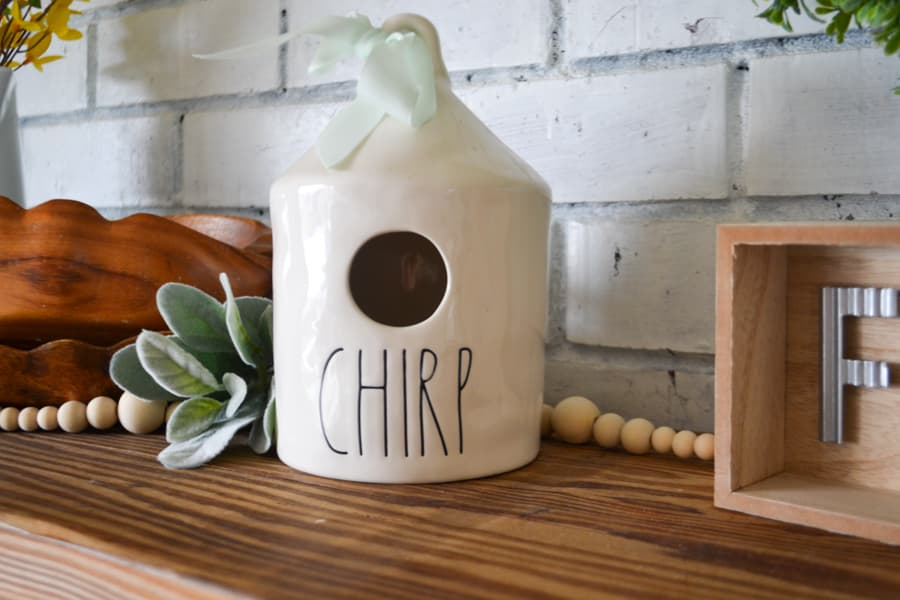 """A close up of a white birdhouse that says """"chirp"""" on a brown mantel with a white brick background"""