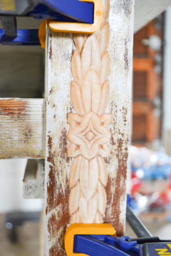 A close up of a carved wood applique unpainted