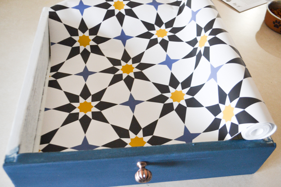 A yellow, white and blue patterned wallpaper being unrolled into a painted drawer