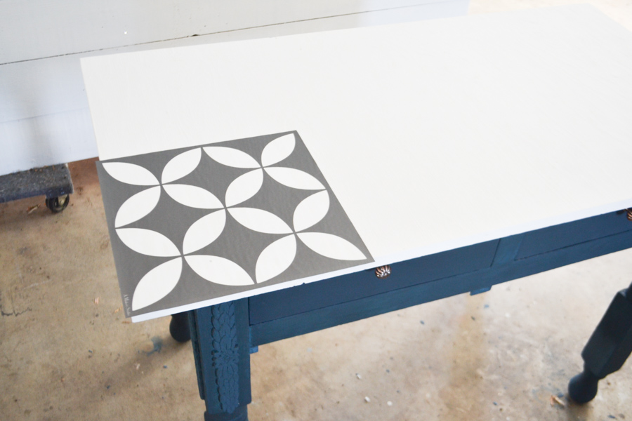 An above view of a stencil laying at the edge of a white tabletop