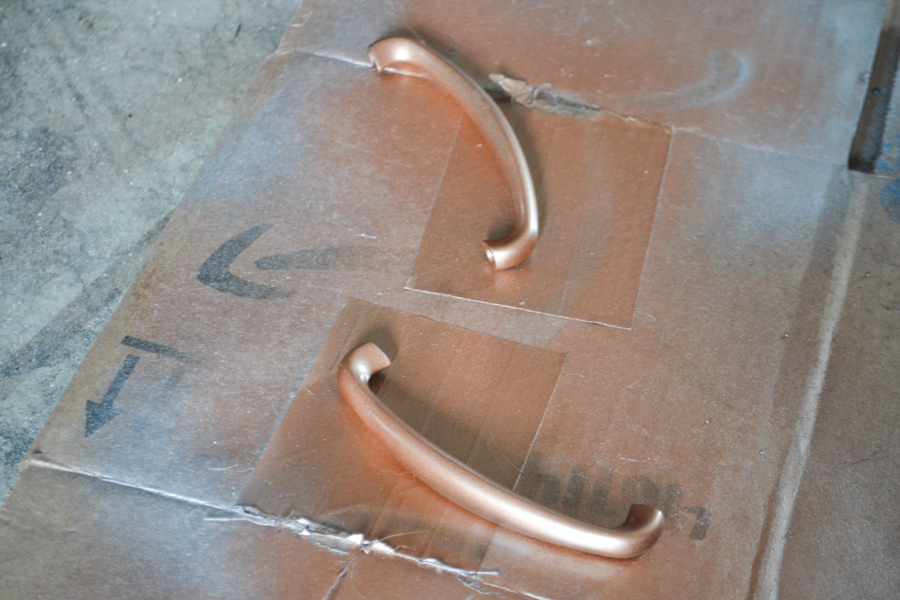 A close up of two long handles painted copper on a piece of cardboard