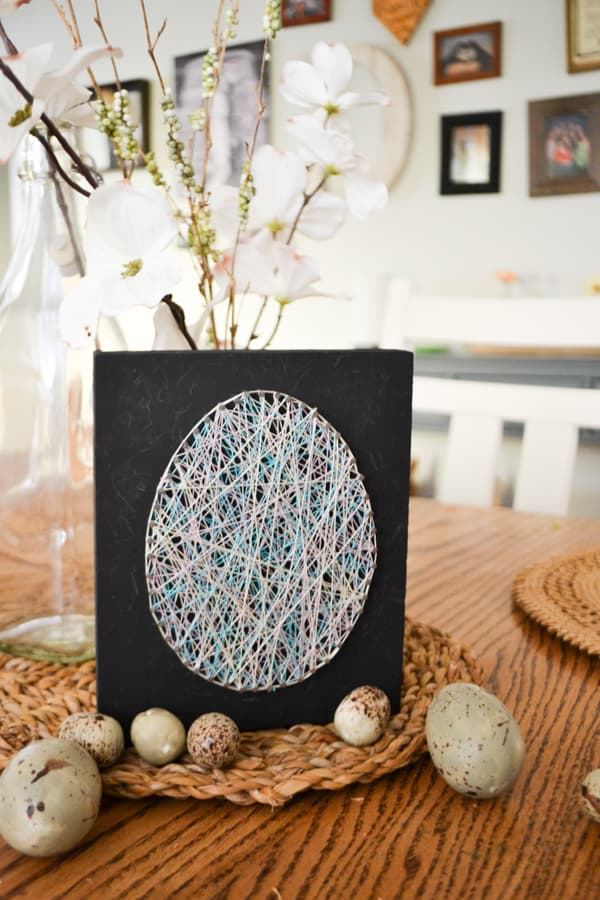An egg string art on a black wood sitting on a table with green speckled eggs in front