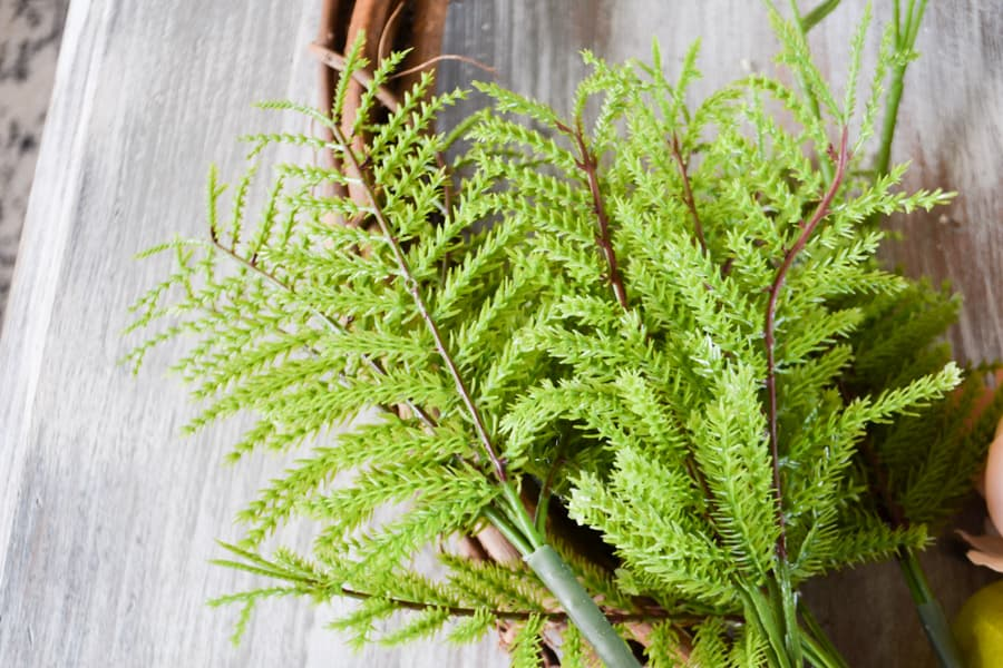 A close up of fake light green ferns laid against a grapeveine wreath on a whitewashed table