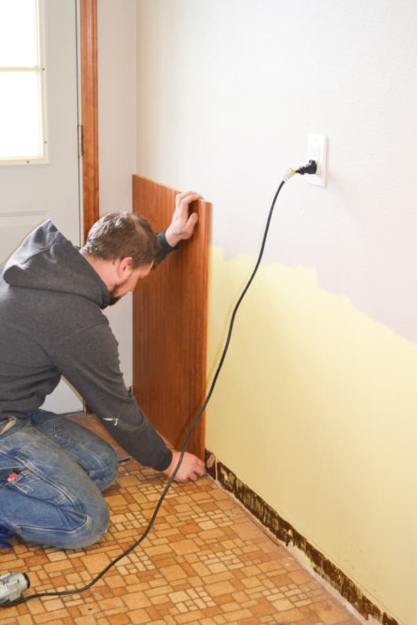 A man kneeling on a brown linoleum instlaling brown wainscotting on a wall