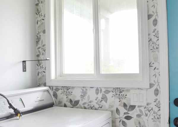 A laundry room wall with the window on the left and a grey floral wallpaper installed