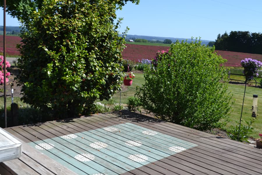 A wood deck with a painted rug