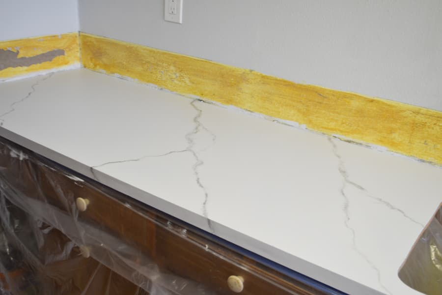 A white painted countertop with grey veining with a yellow background