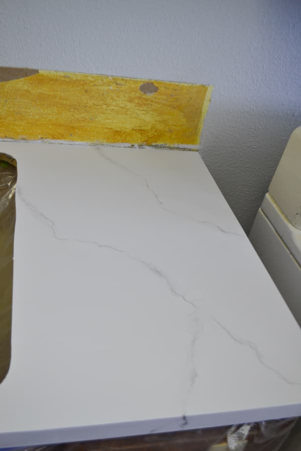 A close up of grey veining on a white countertop with a yellow background
