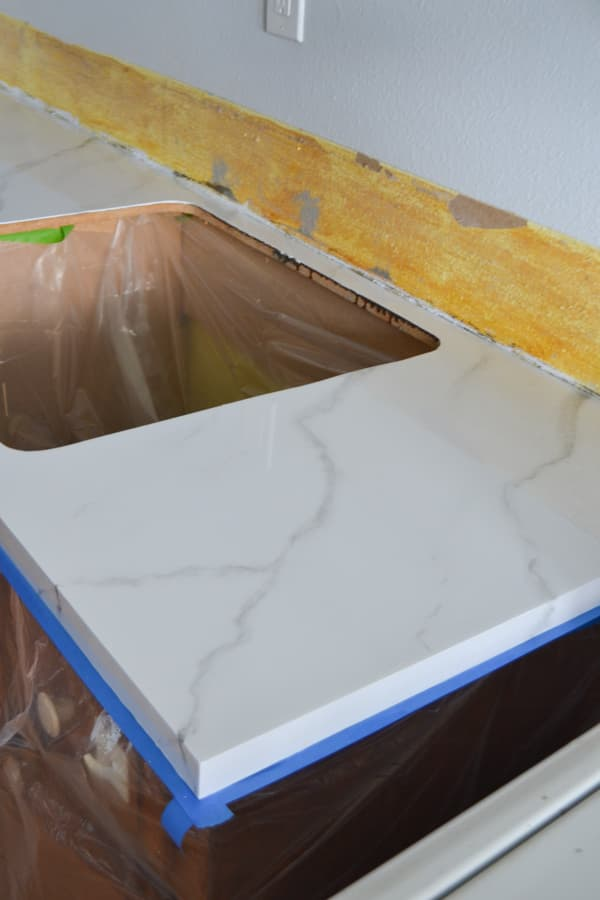 A side view of a painted marble countertop with epoxy shining on top with a sink hole on the left