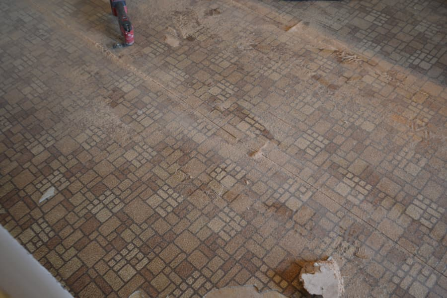 A dusty brown tiled linoleum with lines sawed into the floor