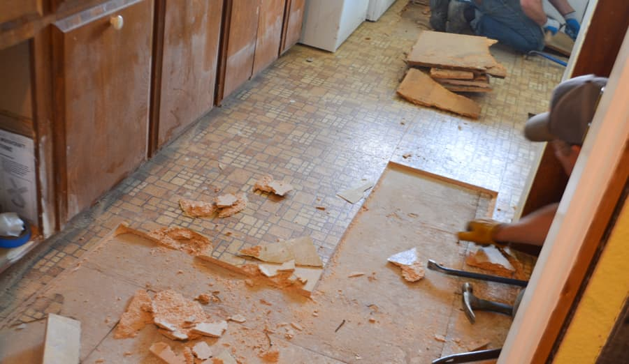 A close up of a brown tiled linoleum floor being tore up with chunks of particle board laying on the floor and a brown cabinet in the background