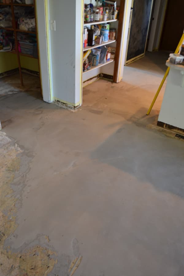 A view into a pantry off a kitchen with a gray flooring