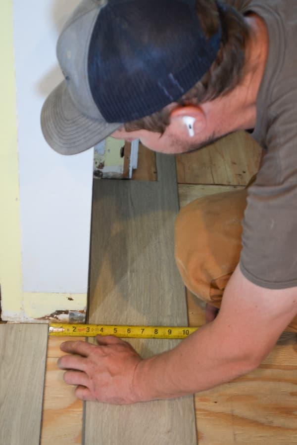 A man kneeling down measuring a piece of gray vinyl plank flooring