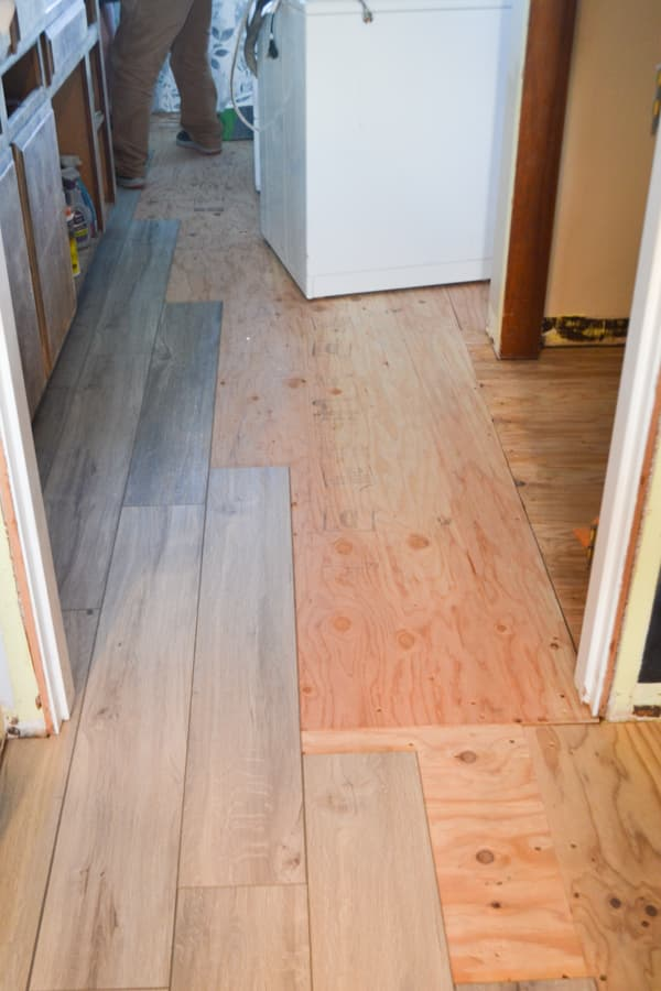 A view into a laundry room with a partial grey vinyl plank flooring laid down
