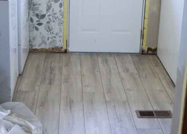 A laundy room with a white door with a window and a grey floral wallpaper with grey flooring