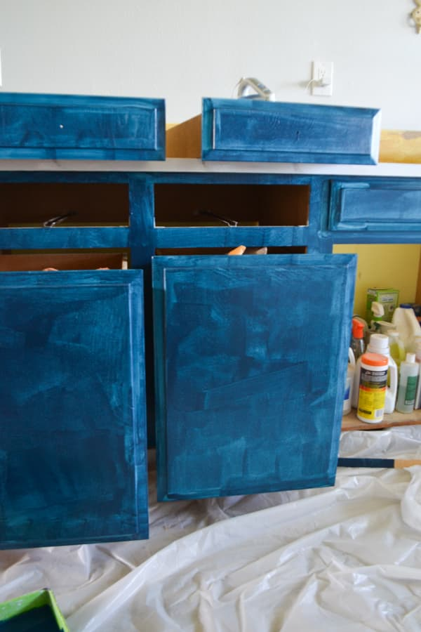A close up of one coat of blue paint on cabinet fronts