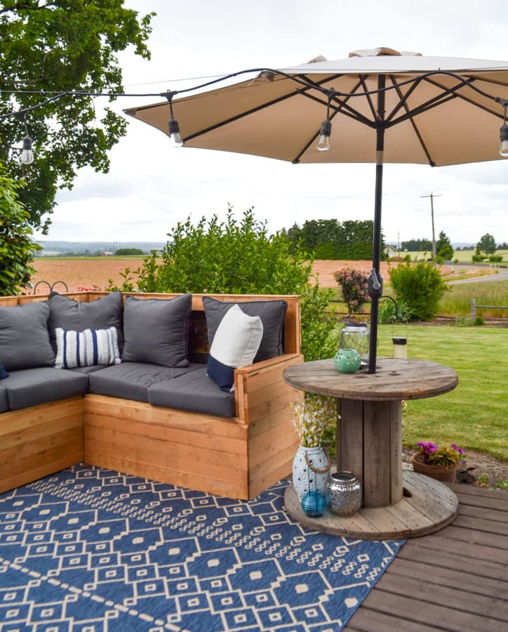 An unfinished wood sectional with dark gray cushions, white pillows and a blue tribal rug with an umbrella up on the right