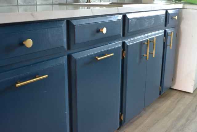 A side view of a blue painted cabinets with gold hardware