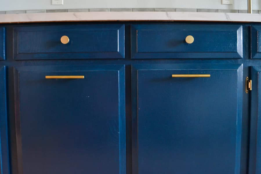 A close up of blue cabinets with gold hardware
