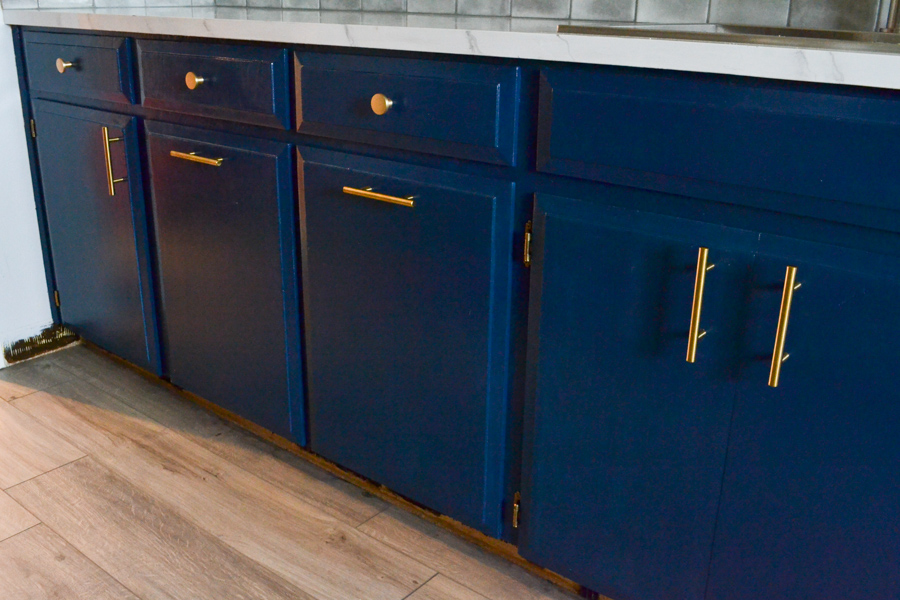 A below view of a blue painted cabinets with gold hardware